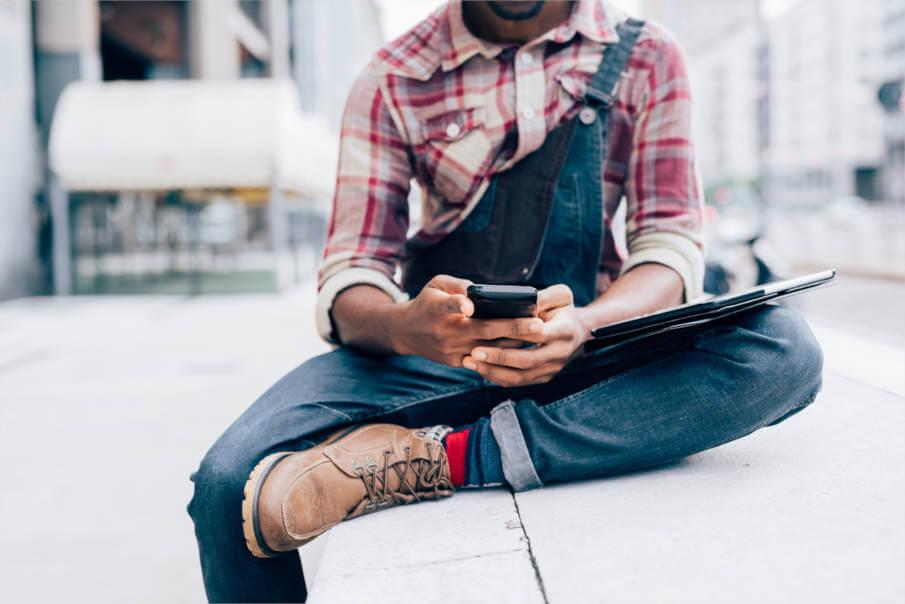 Leder Chelsea-Boots, Mann in Lederboots mit Smartphone in der Hand